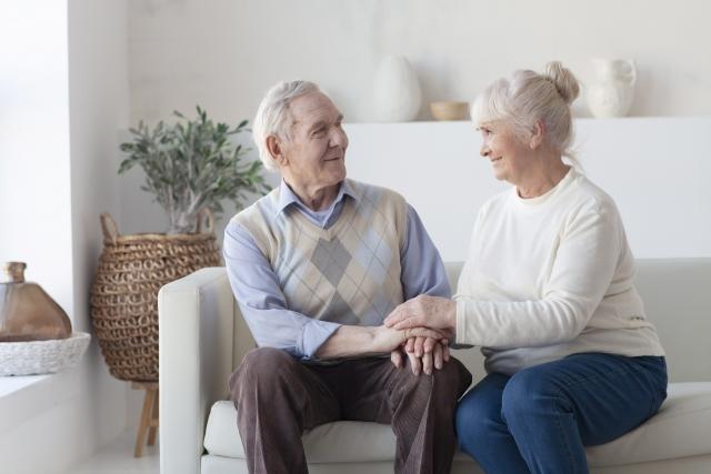 手を取り合い笑顔な老夫婦