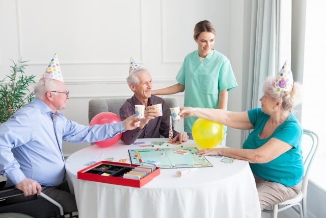 老人ホームで乾杯をしてイベントを楽しむ老人と見守るヘルパー